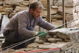 Élève construisant un mur en pierre sèche © Artisans bâtisseurs en pierres sèches